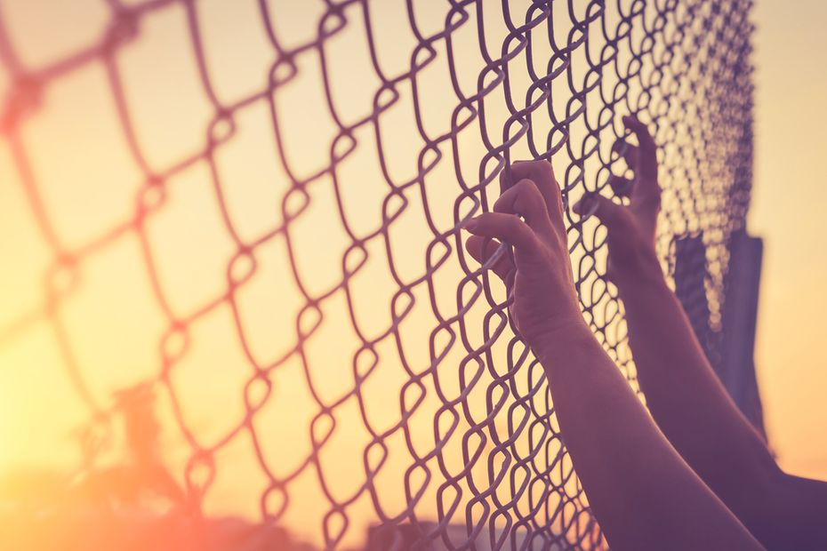 hands on chain link fence